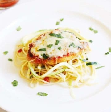 plate of zoodles, with baked chicken parmesan on top parsley as garnish