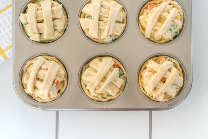 Uncooked pot pies with weaved dough in a criss cross pattern, shown in a muffin tin