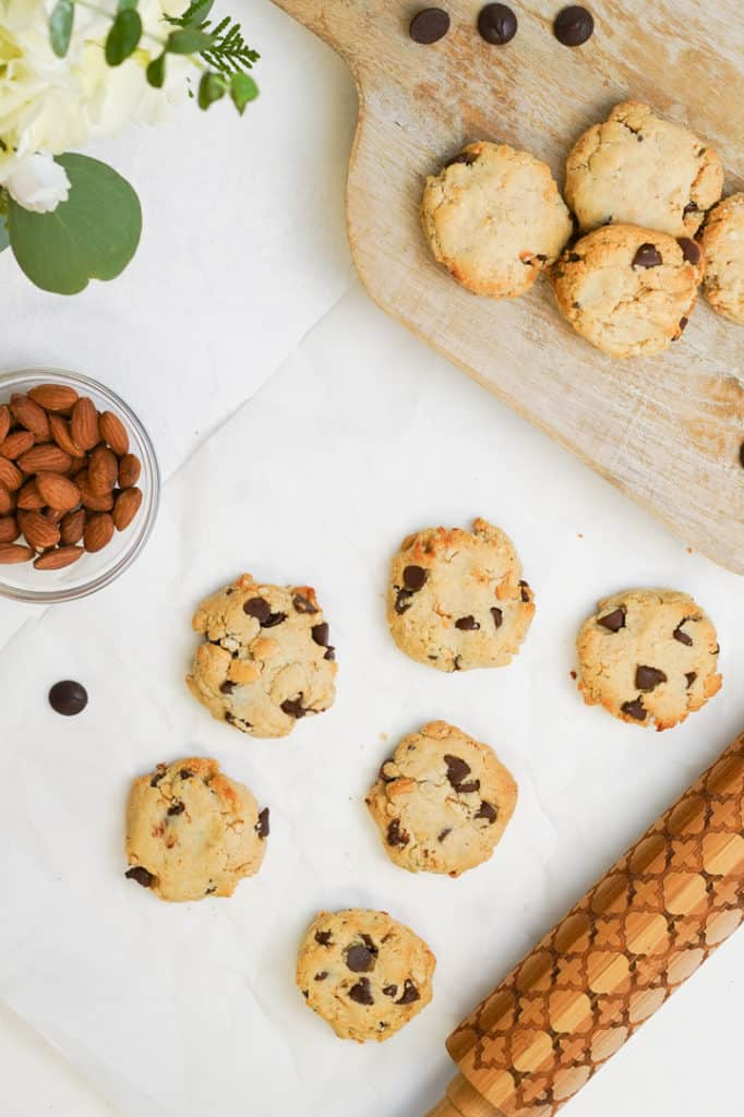 Flat lay of chocolate chip cookies with bowl of almonds and cookies on a wooden board