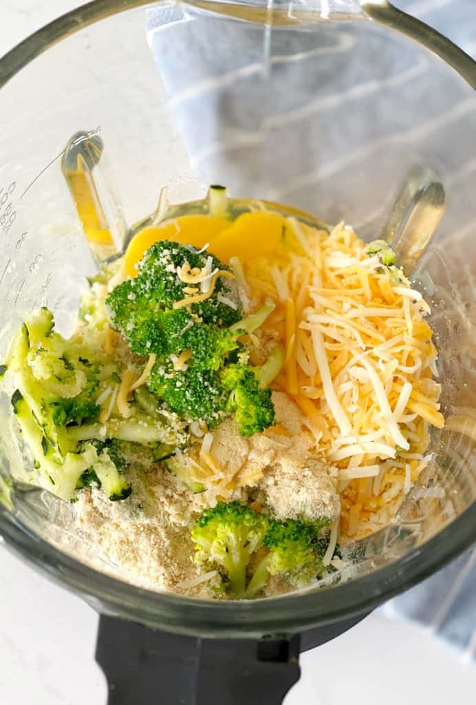 Blender with ingedients including eggs, cheese and broccoli