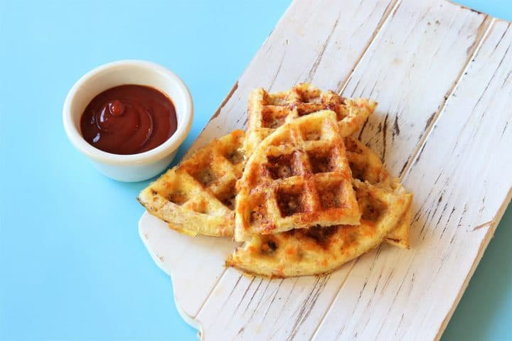 veggie waffles on a board next to ketchup in a bowl