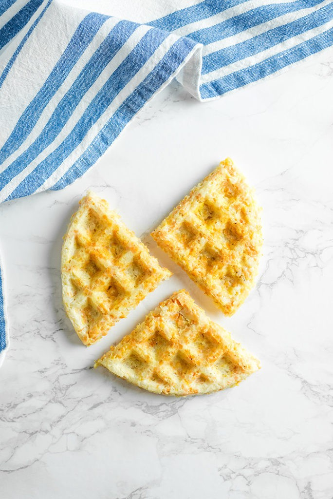 Three waffles on a marble surface with a blue and white kitchen towel on the side