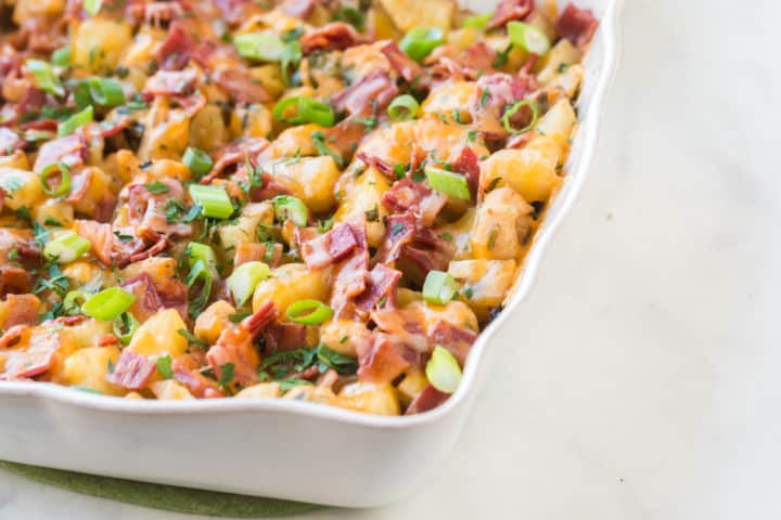 Cooked dish of baked chicken and potatoes with bacon and onion on top