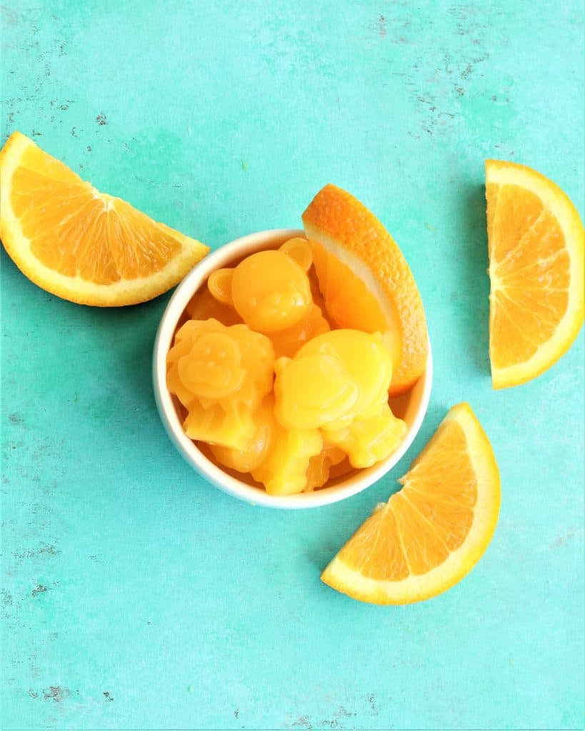 Orange animal jellies next to oranges in a small bowl