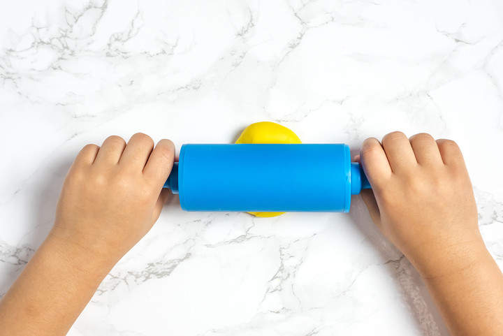Toddler Hands Rolling Play doh with rolling pin