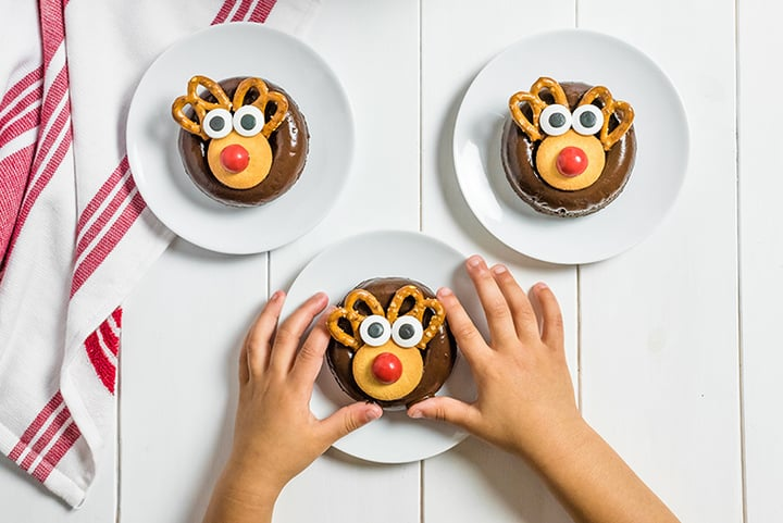 three donuts on a plate with child's hands