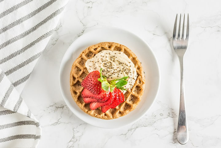 Plate of waffle with strawberries and cream toppings