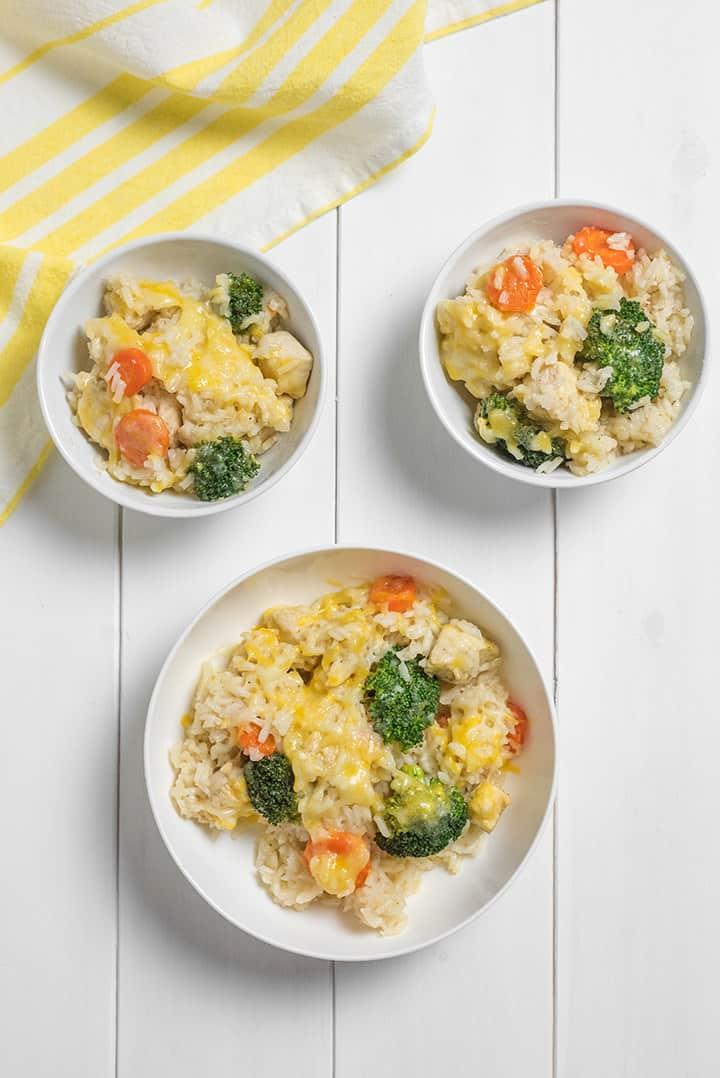 Three bowls of cheesy broccoli chicken and rice