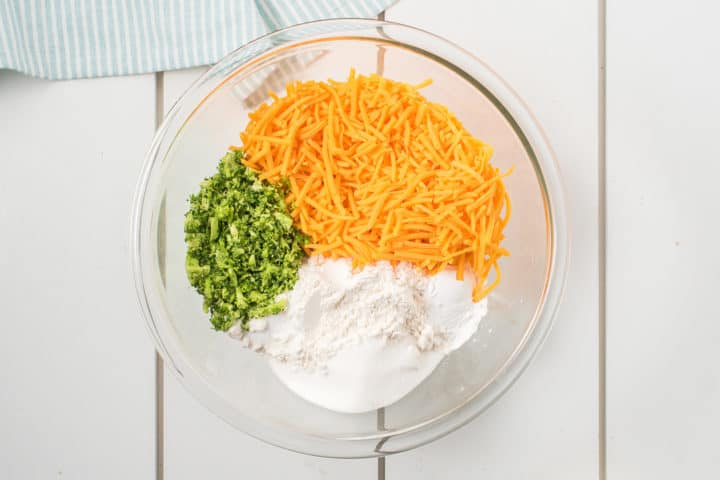 Glass bowl with cheese, broccoli, flour