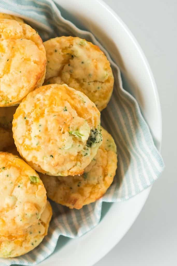 Close up of several broccoli cheese muffins in a white bowl over a teal and white stripe dish towel
