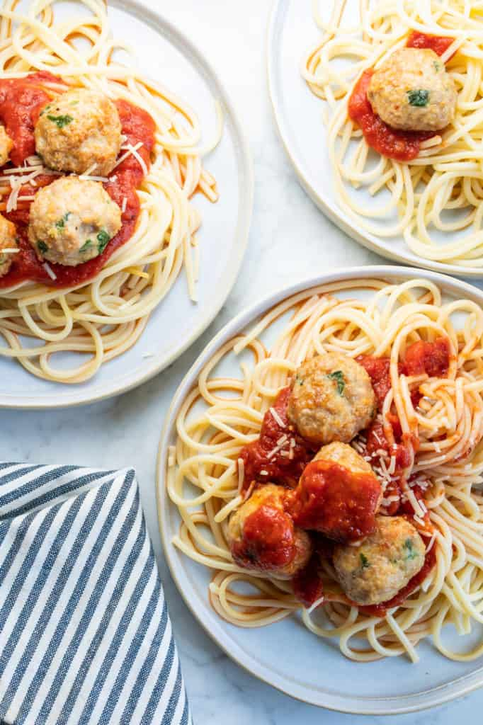 3 plates of spaghetti and meatballs with red sauce, striped gray and white napkin on the side