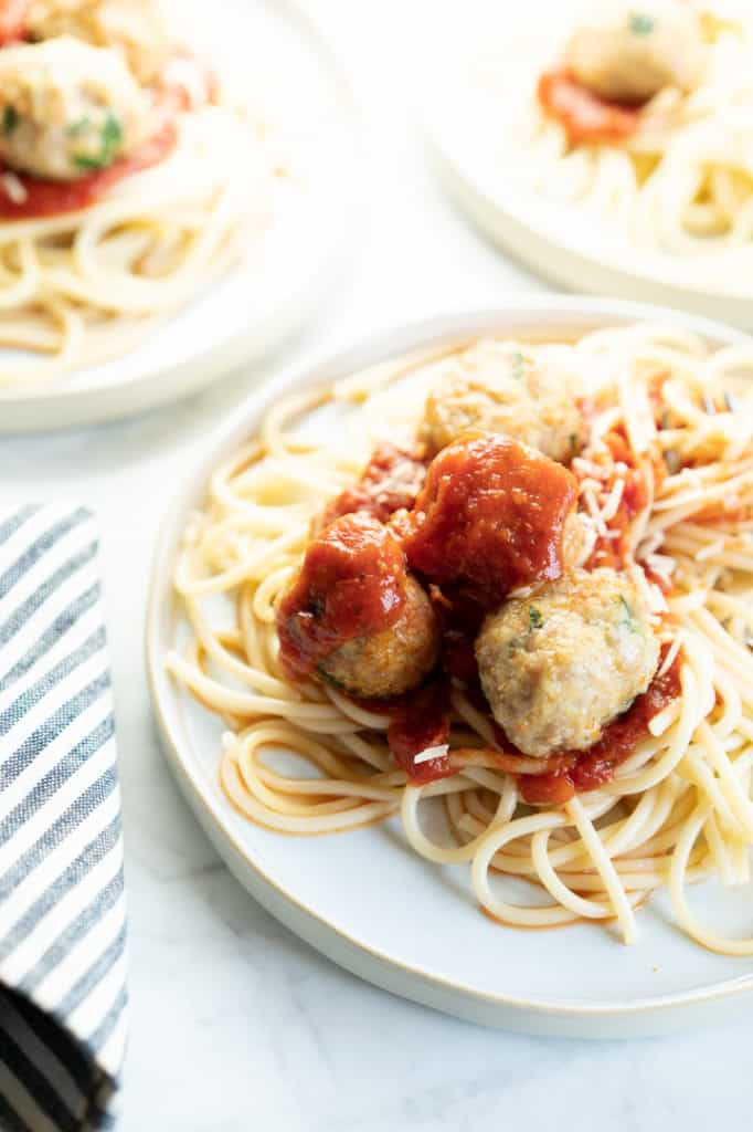 3 plates of spaghetti and meatballs with red sauce on meatballs. Striped napkin