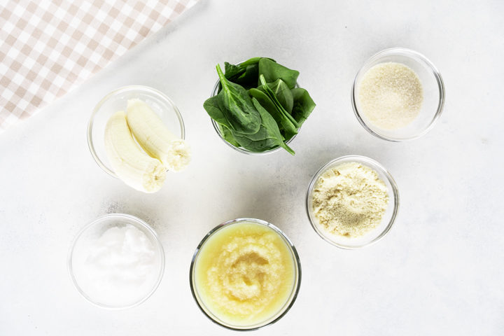 Bowl of banana, bowl of applesauce, bowl of coconut oil, bowl of flour, bowl of sugar, bowl of spinach and gingham napkin on the side