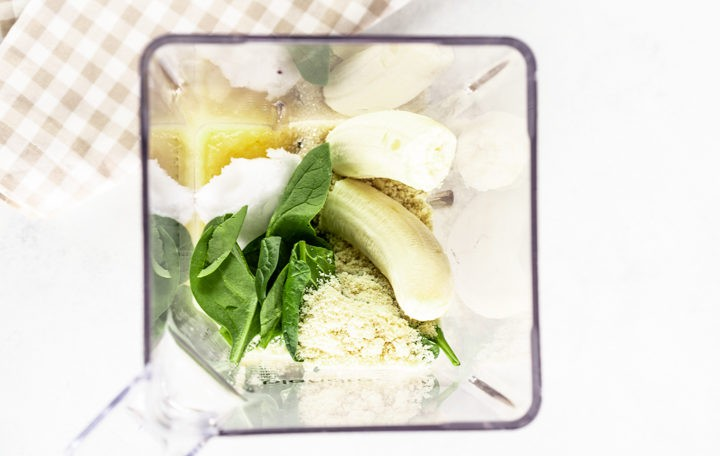 Clear blender with spinach, banana, oil, egg, spinach, applesauce almond meal