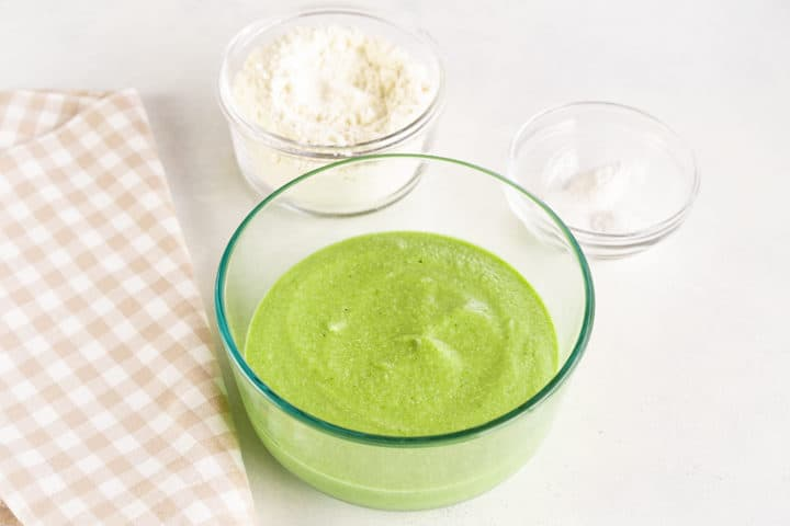 Bowl of green blended mixture, smaller bowls of flour and a bowl of baking powder and soda