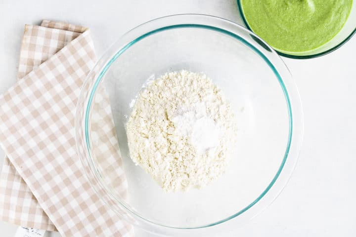 Bowl of flour, and green mixture on the side. A gingham kitchen towel under the bowl