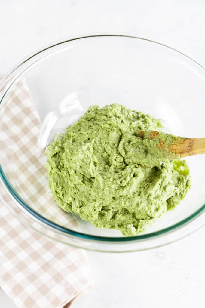 Glass bowl of green mixture with wooden spoon