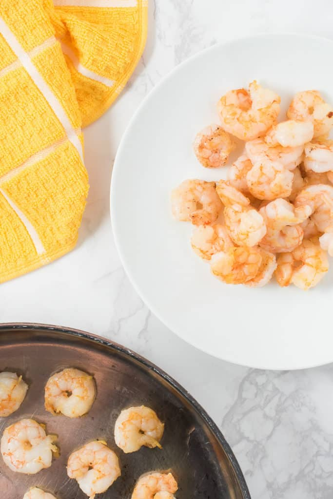 Plate of cooked shrimp next to pan and kitchen towel