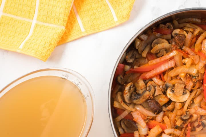 Bowl of stock, sauteed vegetables in a pan and yellow towel