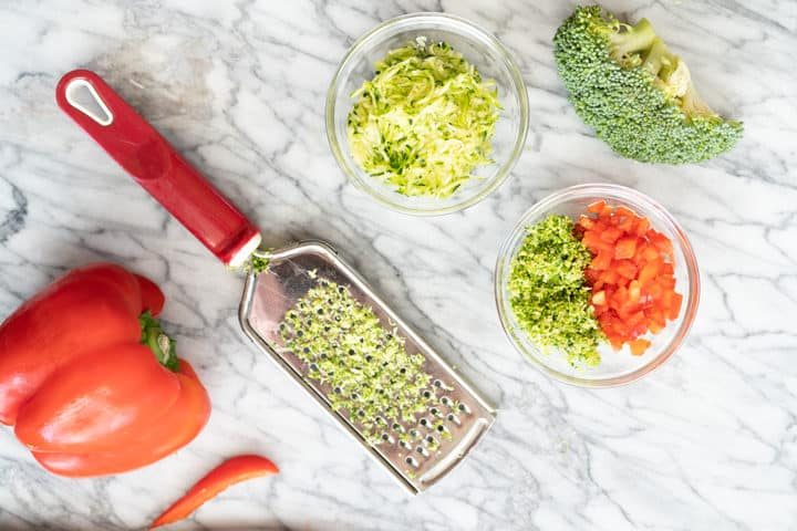Bowl of grated zucchini, broccoli crown, bowl of chopped red bell pepper and grated broccoli, grater with broccoli, red bell pepper