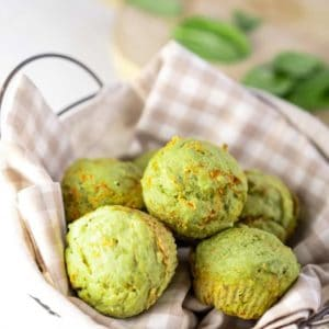 Basket of green spinach muffins on a gingham towel