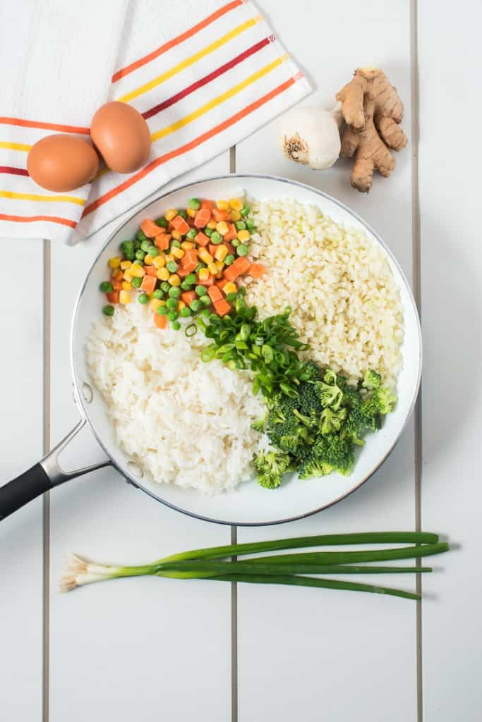 white pan with rices and mixed veggies. Eggs on one side as a prop, green onion and ginger