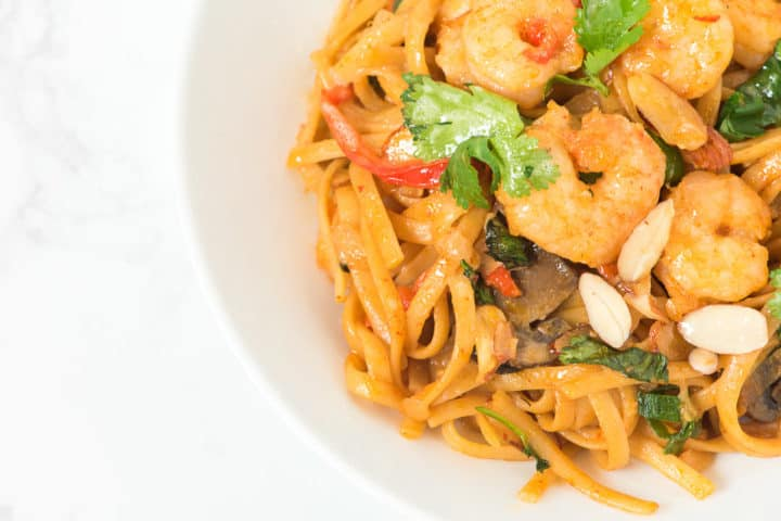 Close up of bowl with noodles and shrimp and garnish