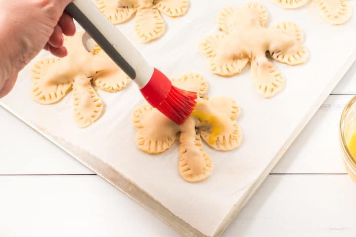 shamrock pie dough sealed with ridge marks on the side and hand brushing shamrock uncooked pie with egg wash