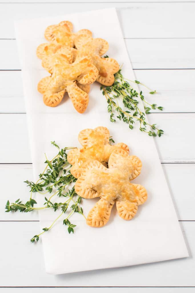 Shamrock hand pies on a white napkin with garnish