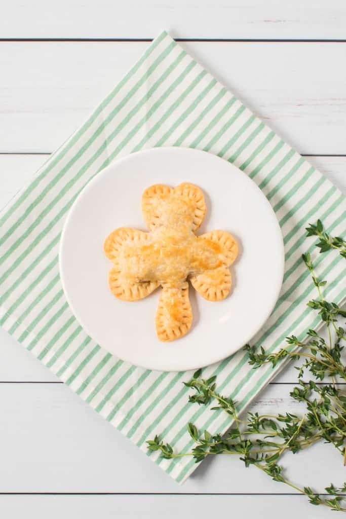 shamrock hand pie on top of white plate. Green and white striped towel with garnish on the side