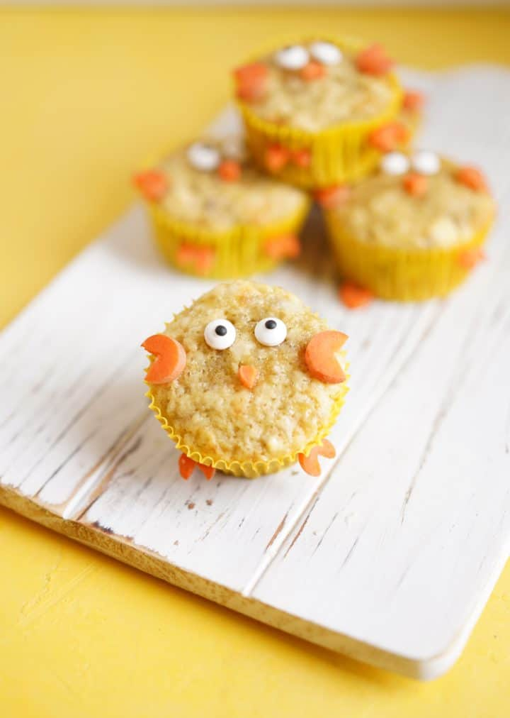 Chick muffin on a white wooden board on a yellow background, muffins in the background