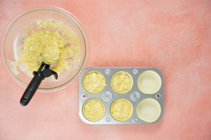 Muffin tin with batter, glass bowl with batter and cookie scoop
