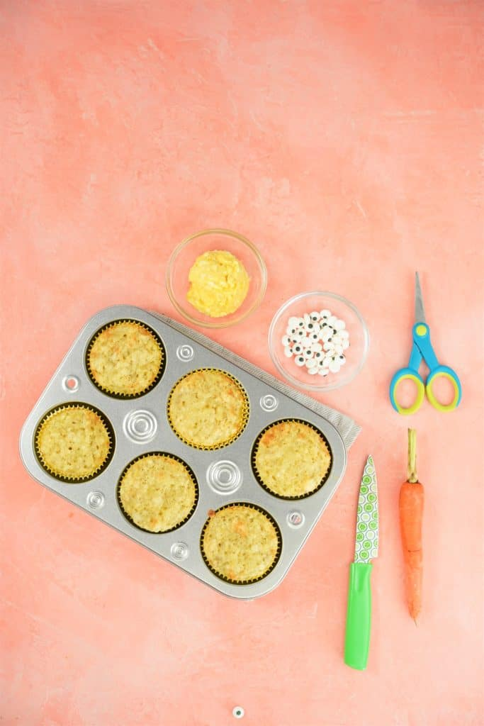 Muffin tin with cooked muffins, bowl of candy eyes, bowl of frosting, sciccors, carrot and knife on side