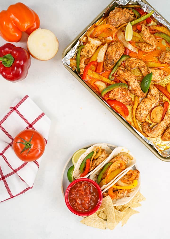 Kitchen towel with tomato on top, fajitas on the side with salsa, sheet pan of chicken onions, bell peppers