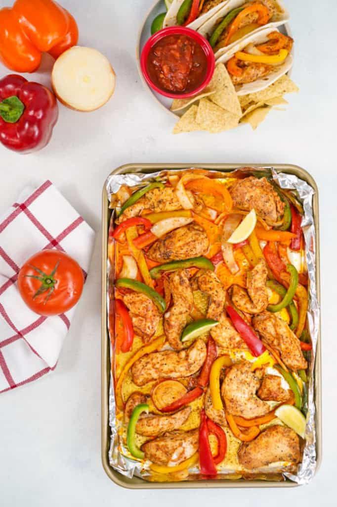 Sheet pan of cooked chicken fajitas with tomato on the side