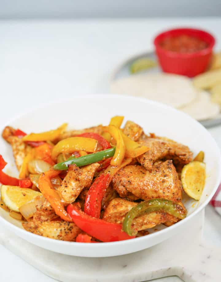 Bowl of cooked chicken and bell peppers with seasoning