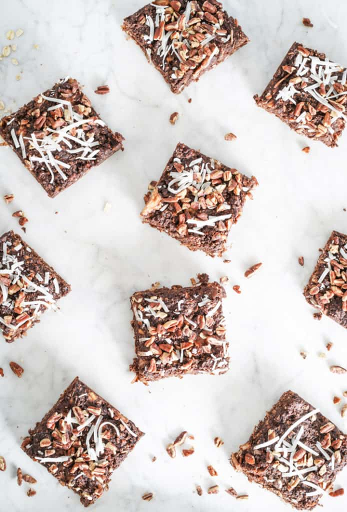 Several square chocolate bars in a flat lay on a marble surface with nuts around