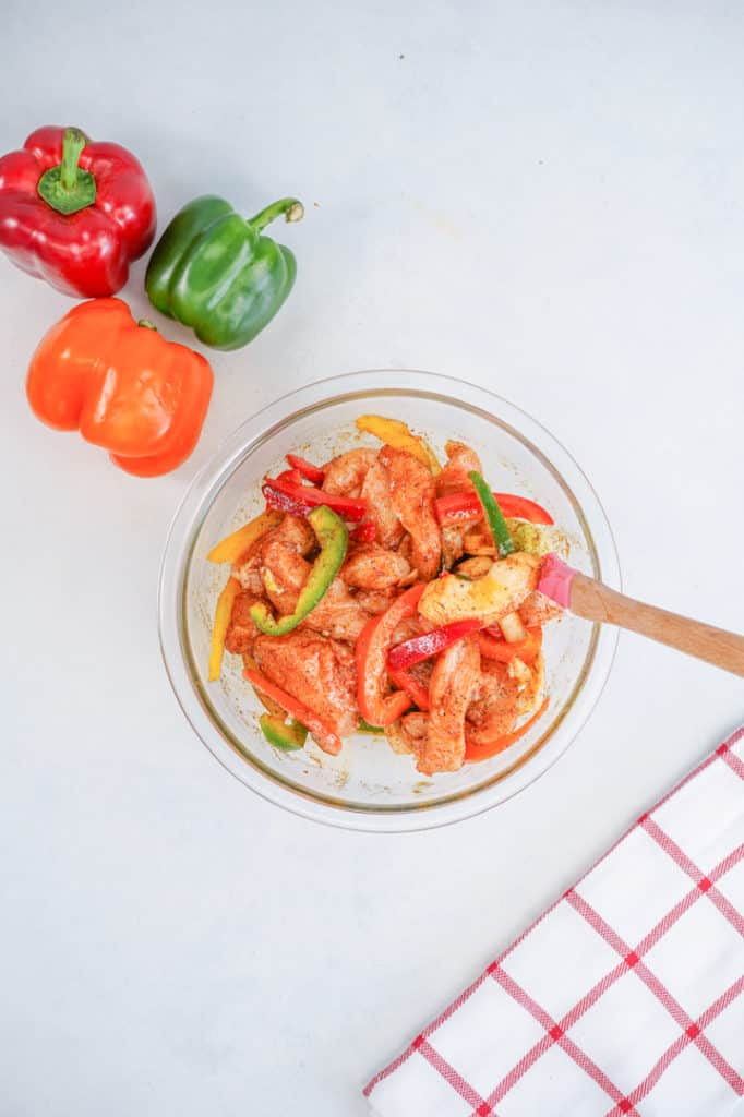 bowl of raw chicken with vegetables in marinade, bell peppers on the side