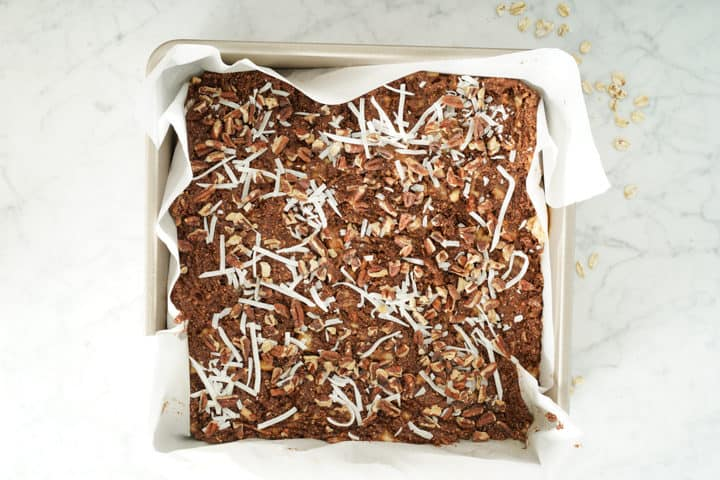 Square chocolate mix in a pan topped with coconut and pecans