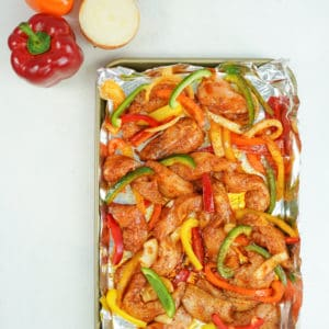 Sheet pan lined with foil with raw chicken and marinated vegetables with onion and bell peppers on the side