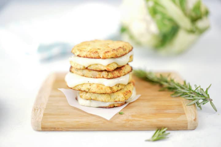 Stack of grilled cauliflower bread and cheese, rosemary sprig on side on top of wooden board