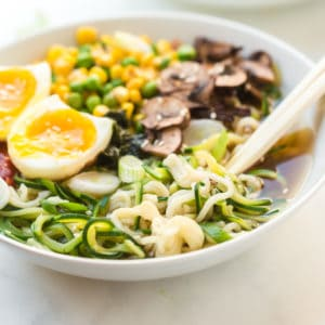Large bowl of ramen with zoodles, vegetables, boiled eggs and mushrooms with chopsticks