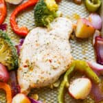 Close up of seasoned chicken next to broccoli, onions, red pepper and potatoes on a sheet pan