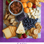 Easy Cheese Board on purple background with fruits, snacks, nuts etc