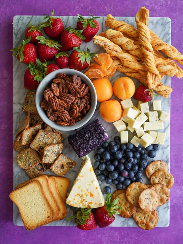 Marble board with snacks including fruit and nuts and cheese