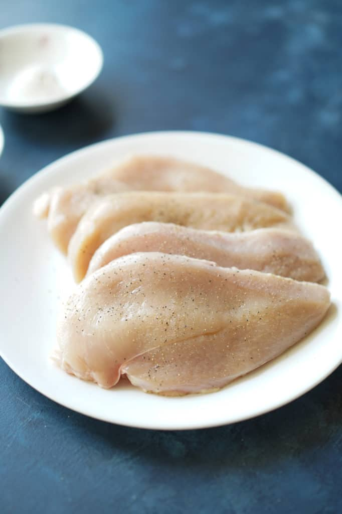 Seasoned raw chicken on plate