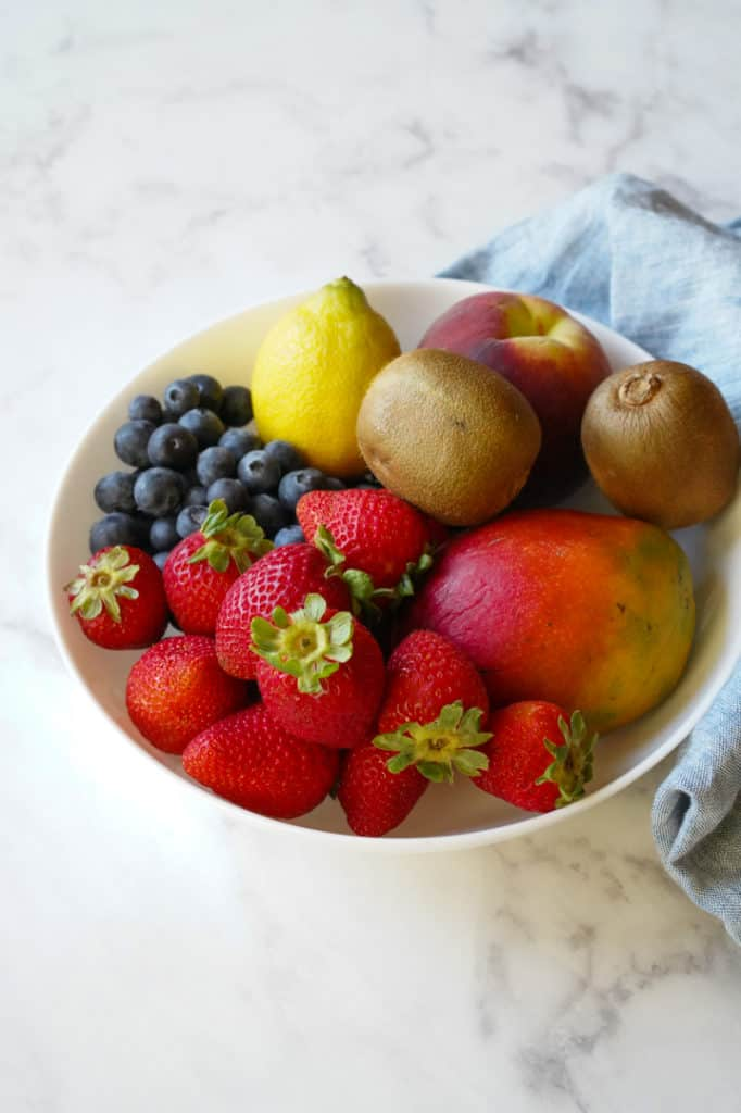 Fresh fruit including strawberries, mango, blueberries, lemon, kiwi and peaches