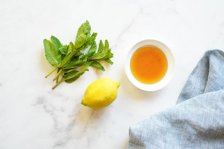 Honey in small bowl, mint leaves, and whole lemon on marble surface