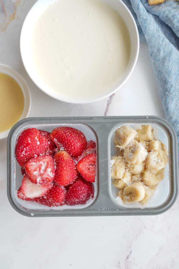 Frozen strawberries and frozen bananas next to heavy cream and condensed milk