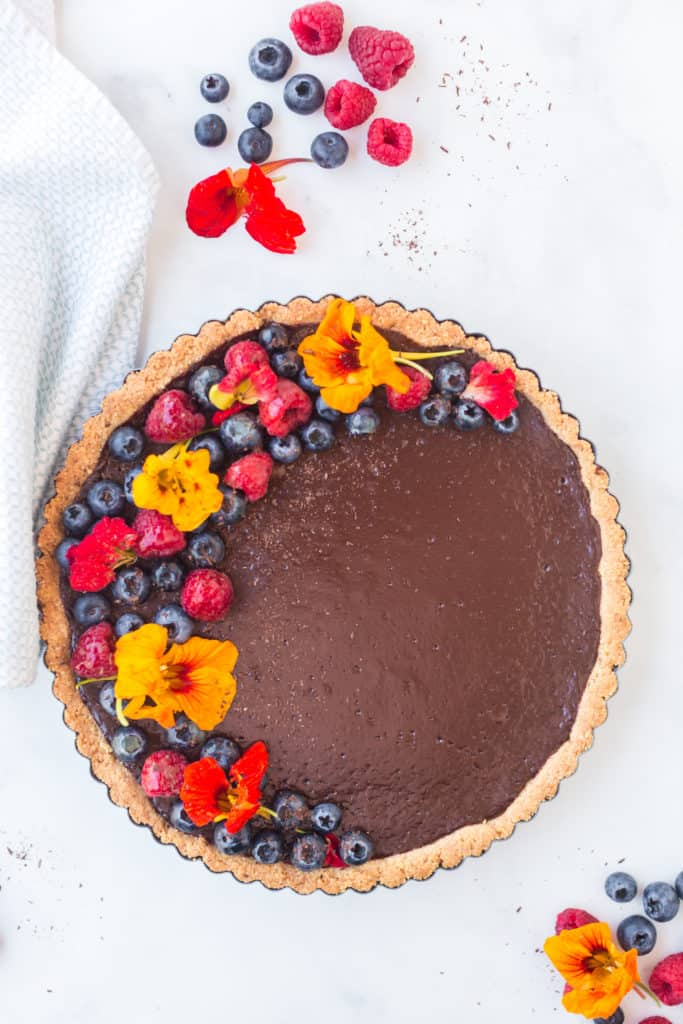 Top down shot of chocolate tart with berries and edible flowers